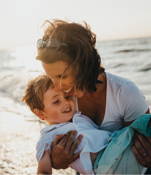 women holding child on the beach